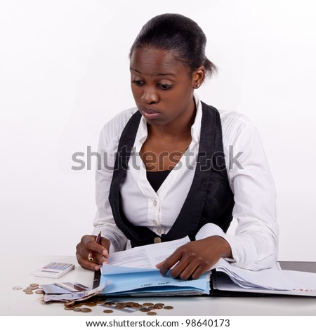 Young woman doing her budget and tired of it, or just worried about her finances! - stock photo