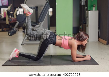 Young woman doing leg exercises while sitting on a gym mat indoor - stock photo