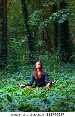 Young woman doing lotus yoga position outside in the forest - stock photo