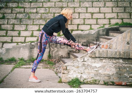Young woman doing relaxation exercise stretching her legs  - stock photo