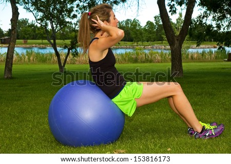 Young woman doing sit ups in a park, on a blue exercise ball. - stock photo