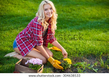 Young woman doing some gardening on a sunny day - stock photo