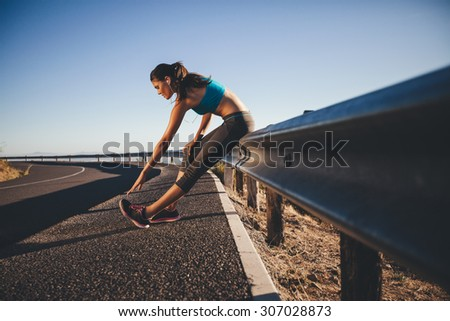 Young woman doing some stretching after a run. Runner leaning on road guardrail relaxing her calf muscles. - stock photo