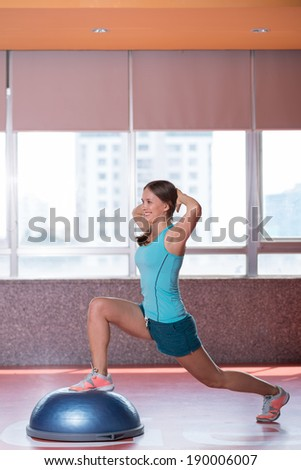 Young woman doing squats on the bosu ball - stock photo