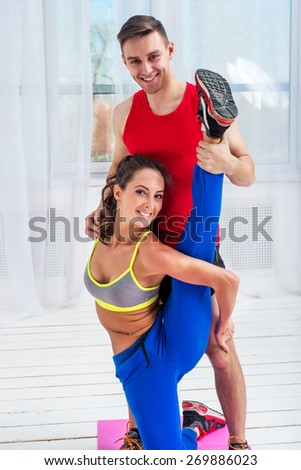Young woman doing streching exercises with man smiling looking at camera concept training exercising workout fitness aerobic. - stock photo