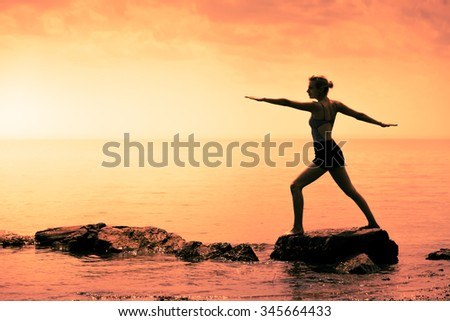 Young Woman doing the Warrior Yoga Position in Front of the Ocean During Sunset - stock photo
