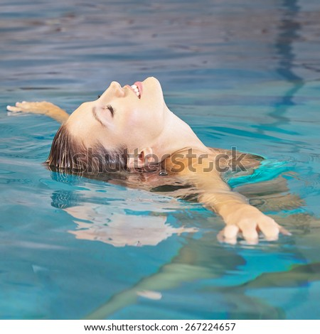 Young woman doing water yoga for relaxation in a swimming pool - stock photo