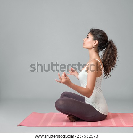Young woman doing yoga and meditating in lotus position - stock photo