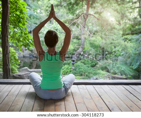 Young woman doing yoga asana in the evening outdoors - stock photo