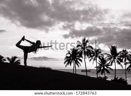 Young woman doing yoga at sunset outdoors - stock photo