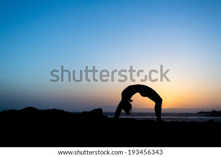 Young woman doing yoga bridge, sunset silhouette in mountains. Sport and fitness stretching exercising outdoors in nature - stock photo