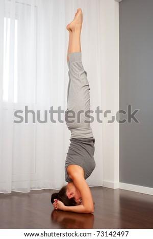 young woman doing yoga exercise on floor - stock photo