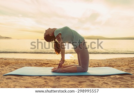 Young woman doing yoga exercise on sand beach on background of sea at sunset in summer - stock photo