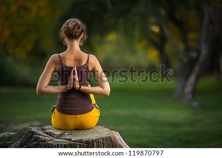 Young woman doing yoga exercises in the autumn city park. - stock photo