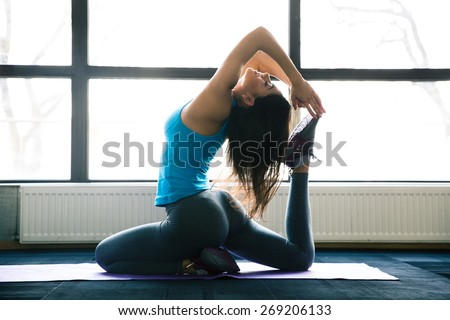 Young woman doing yoga exercises on yoga mat at gym - stock photo