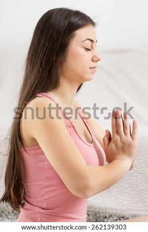 Young Woman Doing Yoga Meditating Relaxing Exercise in prayer position at home.Healthy Lifestyle.Caucasian female practicing meditation on the floor. - stock photo