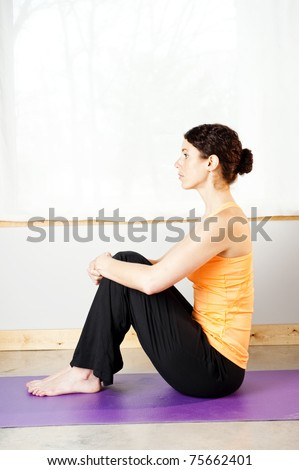 young woman doing yoga on a mat - stock photo