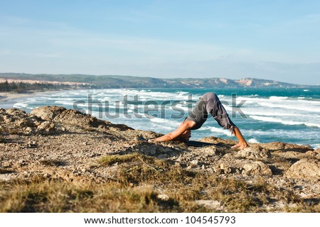Young woman doing yoga on a rocky seashore. Doing downward facing dog pose - stock photo