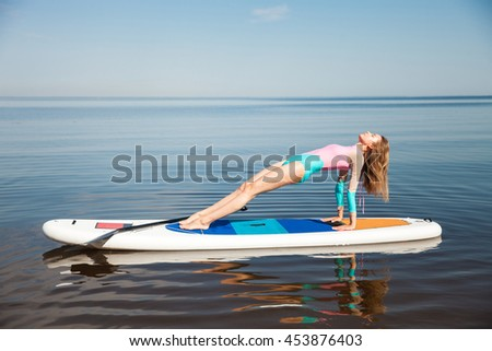 Young woman doing yoga on sup board with paddle. Mediatative pose, side view - concept of harmony with the nature, free and healthy living, freelance, remote business. - stock photo