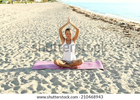 young woman doing yoga on the beach at sunrise.  - stock photo