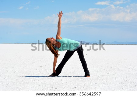 Young woman doing yoga pose on the Bonneville Salt Flats in Utah. - stock photo