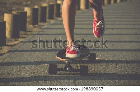Young woman down the street with a skateboard - stock photo