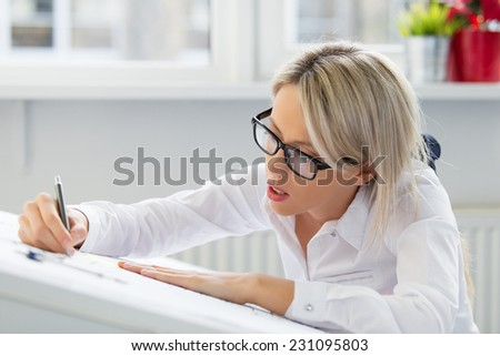 Young woman drawing blueprint - stock photo
