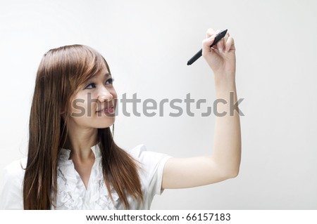 Young woman drawing on grey background - stock photo