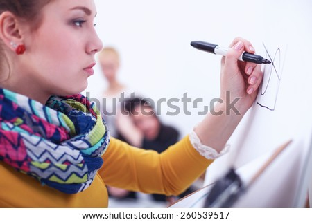 Young woman drawing on wihteboard with white copyspace - stock photo
