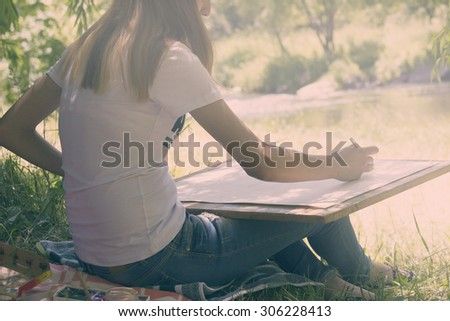Young woman draws on an easel against the river and the forest background - stock photo