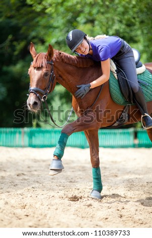 Young  woman  dressage the brown horse - stock photo