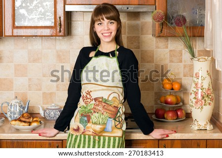 young woman, dressed in apron, leaning on kitchen cupboard - stock photo