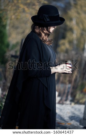 Young woman dressed in black at cemetery holding a candle - stock photo