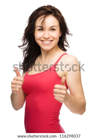 Young woman dressed in red is showing thumb up gesture using both hands, isolated over white - stock photo