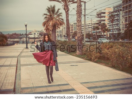 young woman dressed in red skirt and grey blouse posing on the street holding grey bag - stock photo