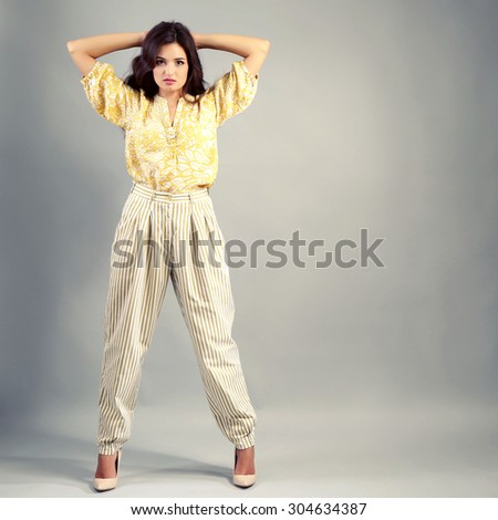 Young woman dressed in retro style on grey background - stock photo