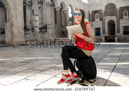 Young woman dressed in sportswear with digital tablet traveling in the old city center. Traveling application concept - stock photo