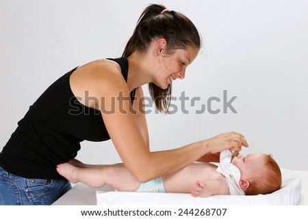 Young woman dressing a baby - stock photo