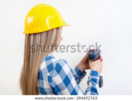 Young woman drilling a hole in the wall and wearing a protective helmet - stock photo