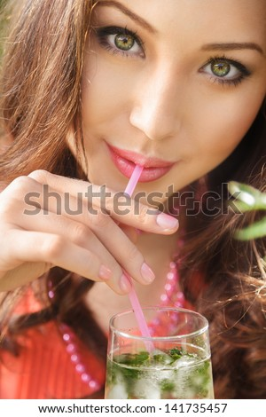 Young woman drink mojito cocktail close-up portrait - stock photo