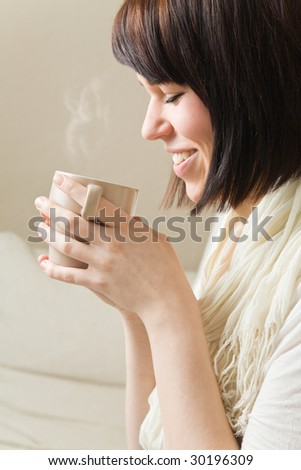 Young woman drinking a hot cup of coffee - stock photo