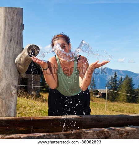 Young woman drinking and playing with water in the alps. - stock photo