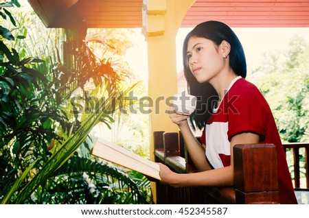 Young woman drinking coffee and reading bookr in cafe. Cafe lifestyle. Casual portrait of teenager girl. Toned. - stock photo