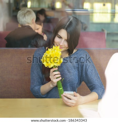 Young woman drinking coffee and use her smartphone sitting indoor in urban cafe. Cafe city lifestyle. Casual portrait of beautiful girl with spring flowers.  - stock photo