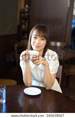 young woman drinking coffee at cafe  - stock photo