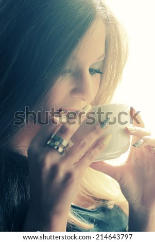 Young woman drinking coffee at home  - stock photo