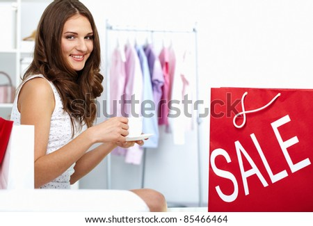 Young woman drinking coffee at shop with shopping bag from sale nearby - stock photo