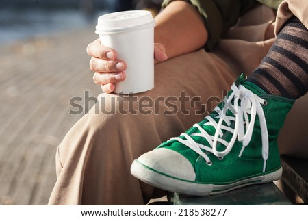 Young woman drinking coffee from am disposable cup - stock photo