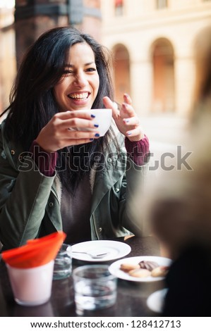 Young woman drinking coffee in a cafe outdoors. Shallow depth of field. - stock photo