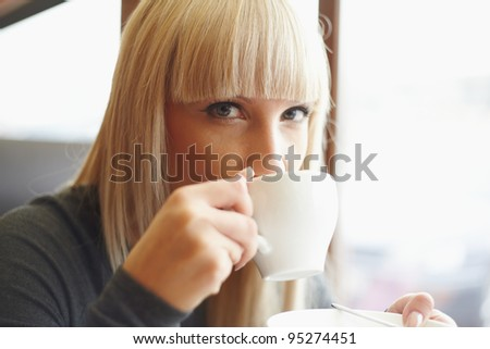 Young woman drinking coffee in cafe - stock photo